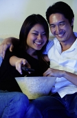 Couple watching TV, woman holding remote control - Asia Images Group