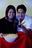 Couple watching TV, woman holding bowl of popcorn, man holding remote control - Asia Images Group