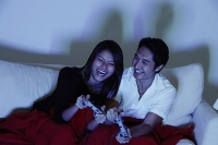 Couple sitting on sofa, playing with video games - Asia Images Group