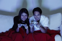 Couple sitting side by side on sofa, playing with video games - Asia Images Group