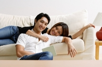 Couple in living room, woman lying on sofa, man sitting on floor in front of her - Asia Images Group