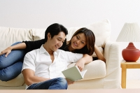 Woman lying on sofa, man sitting on floor in front of her, looking at book - Asia Images Group