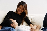 Couple on sofa, man lying on womans lap, smiling at her - Asia Images Group