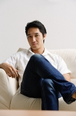 Man sitting on sofa, looking at camera - Asia Images Group