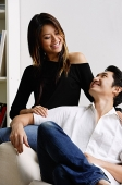 Couple in living room, smiling at each other - Asia Images Group