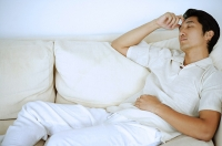 Man lying on sofa, sleeping, hand on head - Asia Images Group