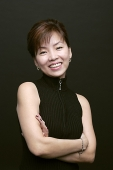 Woman with arms crossed, smiling, looking at camera - Asia Images Group