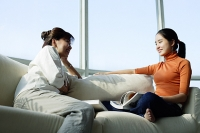 Mother and daughter sitting face to face on sofa - Asia Images Group