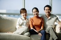 Family with one daughter sitting on sofa - Asia Images Group