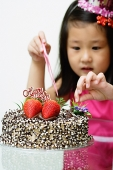 Girl touching birthday cake - Asia Images Group
