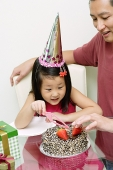 Father and daughter in front of birthday cake, daughter holding cake knife - Asia Images Group
