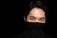 Man with turtleneck over face, looking at camera - Asia Images Group