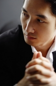 Man looking at away, hands clasped, selective focus - Asia Images Group