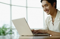 Man sitting, using laptop, smiling - Asia Images Group
