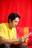 Man using mobile phone, text messaging - Asia Images Group