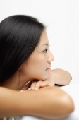 Woman resting head on arms, looking away, profile - Asia Images Group