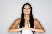 Woman practicing yoga, hands together, eyes closed - Asia Images Group