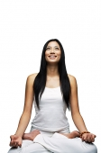 Woman practicing yoga, sitting in lotus position, smiling - Asia Images Group