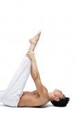 Man doing yoga, lying on back, holding leg - Asia Images Group