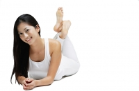 Woman lying on floor, legs crossed at the ankle, smiling at camera - Asia Images Group