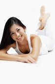 Woman lying on front, legs crossed at the ankle, smiling at camera - Asia Images Group