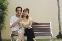 Mature couple sitting on bench, smiling at camera - Asia Images Group