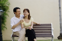 Mature couple sitting on bench, man with arms around woman - Asia Images Group