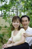Mature couple sitting on bench, woman leaning against man - Asia Images Group