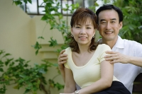 Mature couple sitting together, smiling - Asia Images Group