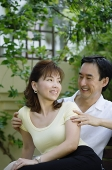 Mature couple sitting together, looking at each other, smiling - Asia Images Group