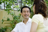 Mature couple sitting, facing each other, smiling - Asia Images Group
