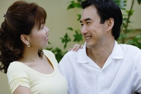 Mature couple side by side, smiling at each other - Asia Images Group