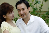 Man smiling at camera, woman smiling at man - Asia Images Group