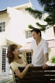 Couple looking at each other, woman sitting on bench, man standing next to her - Asia Images Group