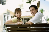 Couple sitting on bench, smiling at camera - Asia Images Group