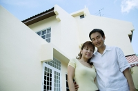 Couple standing in front of house, arms around each other - Asia Images Group