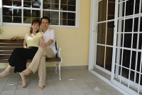 Couple sitting on bench in patio, holding hands - Asia Images Group