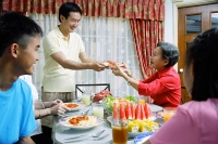 Adult son passing plate of food to senior woman - Asia Images Group