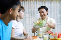 Father passing salad bowl to family members - Asia Images Group