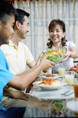 Mother passing salad bowl to family members - Asia Images Group