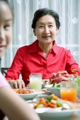 Senior adult at dining table, smiling at camera, granddaughter in the foreground - Asia Images Group