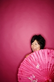 Woman behind pink umbrella, against pink background - Asia Images Group