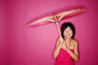 Woman holding umbrella, standing against pink background - Asia Images Group