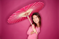 Woman with umbrella, standing against pink background - Asia Images Group