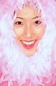 Womans smiling face surrounded by feathers - Asia Images Group