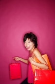 Young woman against pink background carrying shopping bags - Asia Images Group