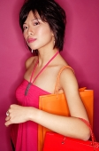 Young woman carrying shopping bags, looking at camera - Asia Images Group