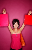 Young woman against pink background holding up shopping bags - Asia Images Group