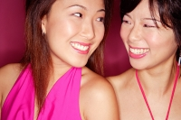 Two young women side by side smiling at each other - Asia Images Group