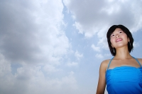 Young woman standing, looking away, low angle view - Asia Images Group